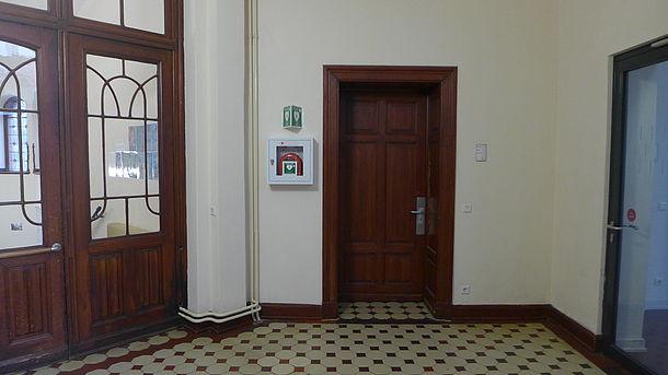Nach Eingangstür links, AED Standort